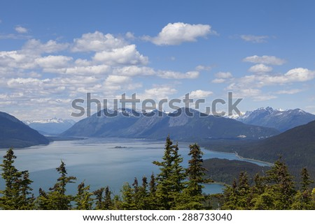 View of the Chilkat Inlet near Haines Alaska from a mountain in summer with puffy clouds. - stock photo