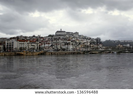 View of the city of Coimbra, Portugal and river under dark skies