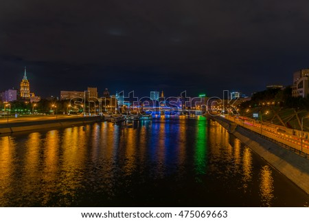 view of the city of Moscow in Russia from moscova river at night with the bridges and buildings illuminated reflected in water