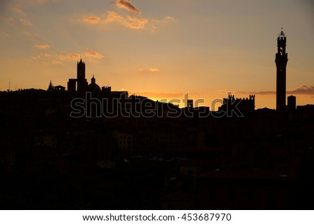 view of the city of Siena at sunset with the towers and the Gothic cathedral of white marble