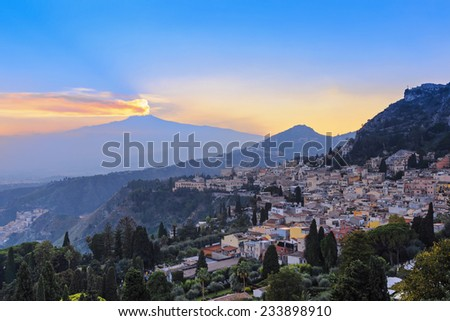 View of the city of Taormina and the active volcano Etna at sunset, Italy - stock photo