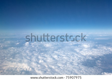 View of the clouds from the airplane in flight. - stock photo