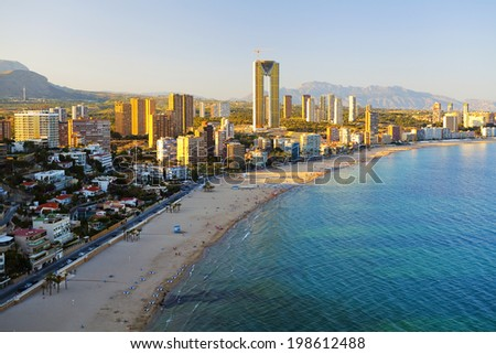 View of the coast and the city with having a rest people at sunset (Spain, Benidorm) - stock photo