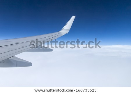 View of the dense clouds and wing of an airplane window