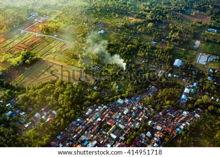 view of the earth landscape, Manado city, from an airplane above the clouds, Indonesia - stock photo