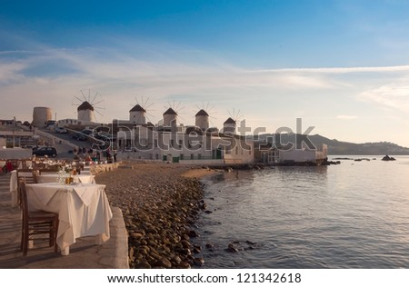 View of the famous windmills of Mykonos from  restaurant at Little Venice. Greece. - stock photo