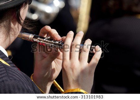 View of the fingers of a young woman playing a flute on a dark background. Girl playing a flute.