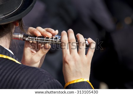 View of the fingers of a young woman playing a flute on a dark background. Playing a flute