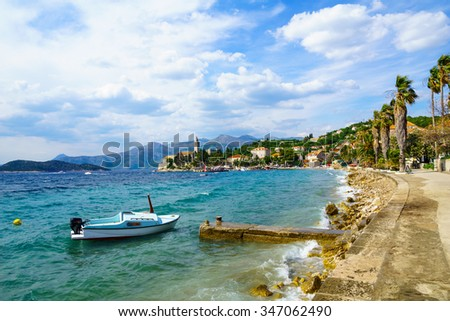 View of the fishing port and the beach, with cafes, boats, in the village Lopud, Lopud Island, one of the Elaphiti Islands, Croatia - stock photo