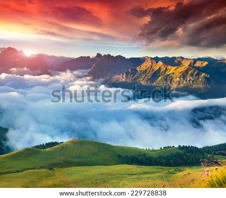 View of the foggy Val di Fassa valley with passo Sella. National Park. Dolomites, South Tyrol. Location Canazei, Campitello, Mazzin. Italy, Europe. Dramatic sky. - stock photo