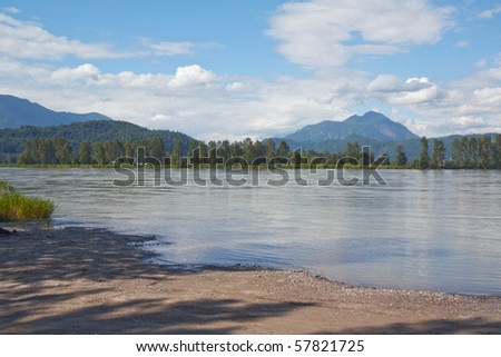 View of the Fraser River in British Columbia, Canada, with blue sky and white clouds - stock photo