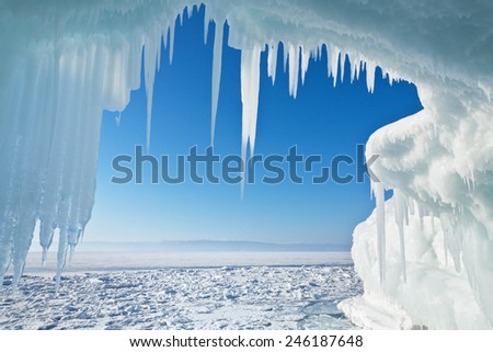 View of the frozen Lake Baikal through the ice arch with icicles