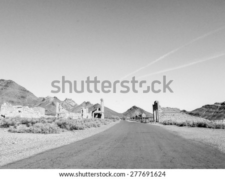 View of the ghost town of Rhyolite in Death Valley Nevada USA with ruins of the old bank, school and railway station in black and white - stock photo