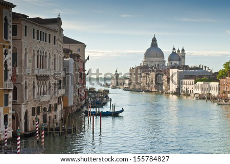 View of the Grand Canal and the stunning baroque Santa Maria Della Salute (1687) church in Venice and colourful villas bathed in early morning light.