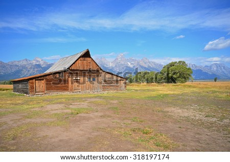 view of the Grand Tetons with historic barn in foreground - stock photo