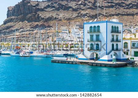 View of the harbor of Puerto de Mogan from the ocean - stock photo