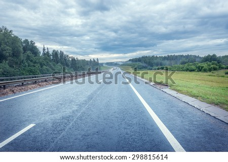 View of the highway at foggy autumn morning time. - stock photo