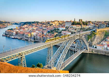 View of the historic city of Porto, Portugal with the Dom Luiz bridge. A metro train can be seen on the bridge - stock photo