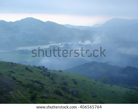 View of the horizon with smoking recent lava flows and green grass in view, near Antigua, Guatemala - stock photo