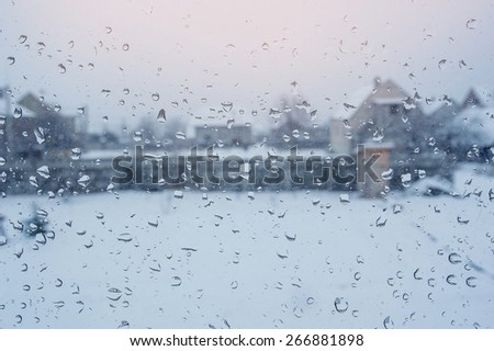 View of the houses through a window with raindrops. - stock photo