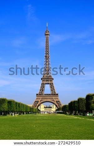 View of the iconic Paris landmark, the Eiffel Tower from Champ de Mars, with vibrant blue sky, France