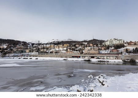 View of the icy Sankt Moritz lake and the city on the mountain in Winter, Grisons, Switzerland