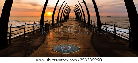 View of the Indian Ocean through the Millenium Pier in Umhlanga Rocks at Sunrise - stock photo