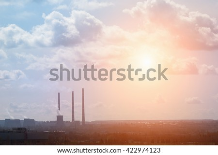 View of the industrial city and the sky with clouds and sun