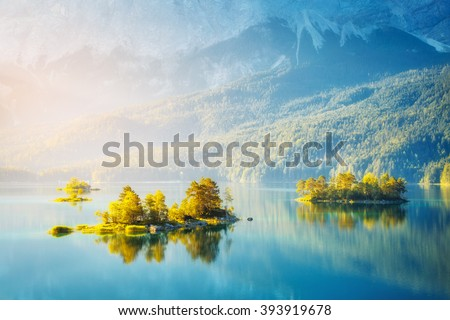 View of the islands and turquoise water at Eibsee Lake at the foot of Mt. Zugspitze. Morning scene. Location famous resort Garmisch-Partenkirchen, Bavarian alp, Europe. Artistic picture. Beauty world. - stock photo