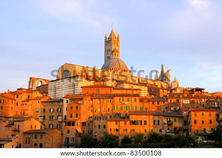 View of the Italian hill town of Siena under the glow of the setting sun - stock photo