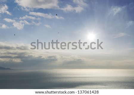 View of the Kachemak Bay in Alaska on a calm day with a sunburst, light glowing on the water, clouds and blue sky. - stock photo