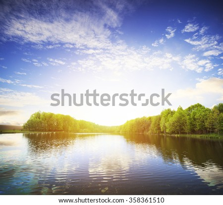 View of the lake with green coast and clouds and bright sun