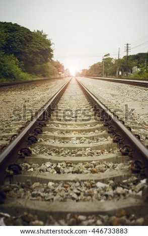 "view of the length of railway with green tree at left and right side of railway,filtered image, light effect and flare added,selective focus,mean ""There light at the end of the tunnel"", success way"
