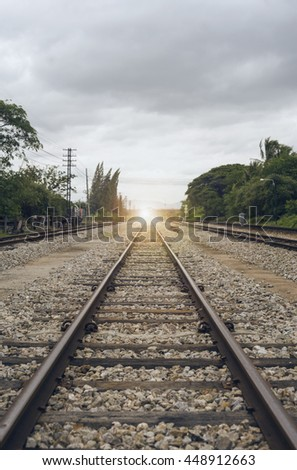 "view of the length of railway with green tree at left and right side of railway,filtered image, light effect and flare added,selective focus,mean ""Theres light at the end of the tunnel"", success way"