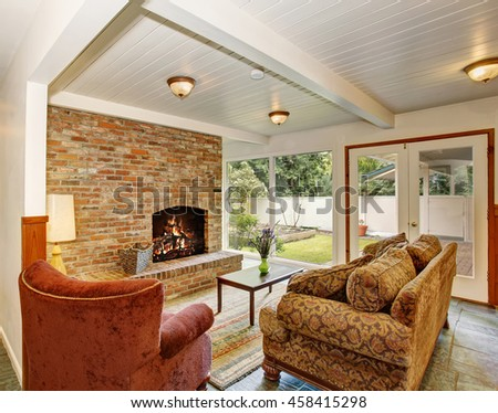 View of the living room area with white wooden ceiling and brick wall with fireplace. French doors leading to the vegetable garden. - stock photo