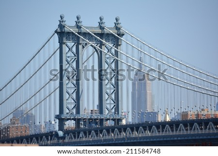 View of the Manhattan Bridge and Empire State Building as seen from the Brooklyn Bridge. - stock photo