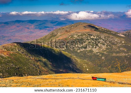 View of The Mount Washington Cog Railway and distant ridges of the White Mountains from the summit of Mount Washington, New Hampshire. - stock photo
