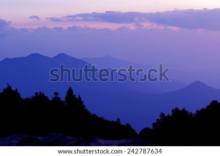 view of the mountain range in the evening with the dark cloud background - stock photo