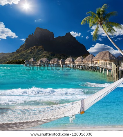 View of the mountain through the palms, hammock, houses on water and ocean. - stock photo