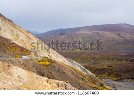 View of the mountains from Polychrome Pass in Denali National Park showing one of the tour buses on the dirt road - stock photo