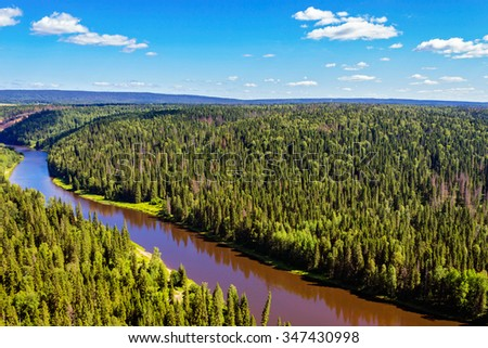 View of the northern spruce forest and river from above. Russia