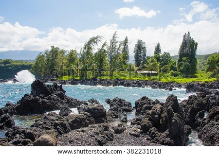 View of the ocean from the black sand beach in Hawaii on Maui island - stock photo