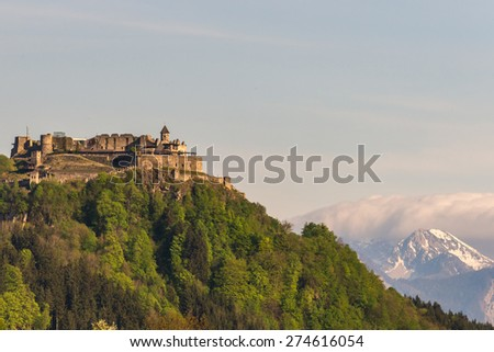 View of the old medieval castle of Landskron in Villach/Austria, located on top of a hill surrounded by a forest, in front of the Karawanks Mountains including prominent Mt. Kepa - stock photo