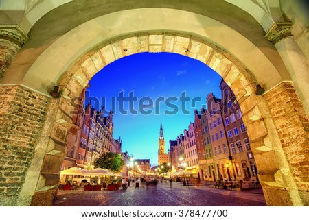 View of the old town of Gdansk with the Main Town Hall through the arch of Green Gate in the evening, Poland - stock photo