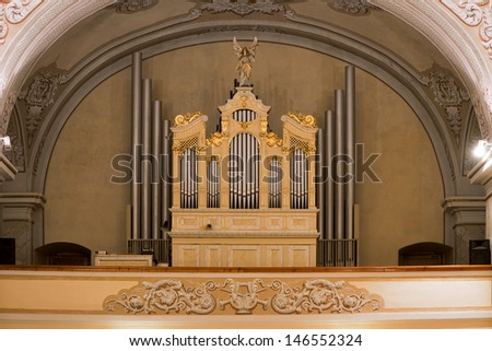 View of the organ in the Catholic church, with gold ornaments and angels with trumpets - stock photo