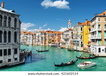 View of the Palazzo dei Camerlenghi and the Grand Canal with gondolas and water taxi from the Rialto Bridge in Venice, Italy. Venice is a popular tourist destination of Europe.