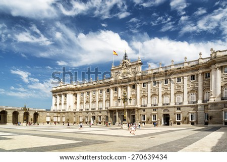 View of the Plaza de la Armeria and the south facade of the Royal Palace of Madrid on the blue sky background with white clouds in Spain. Madrid is a popular tourist destination of Europe. - stock photo
