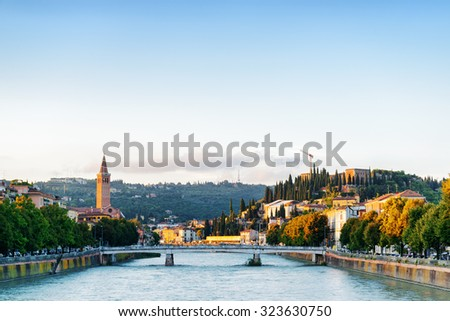 View of the Ponte Nuovo (New Bridge) over the Adige River in Verona (Italy) at dawn. Blue sky in background. Verona is a popular tourist destination of Europe. - stock photo