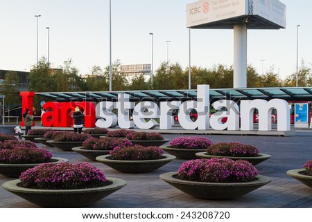View of the red and white I am Amsterdam sign at the arrival/departure deck at Schiphol airport. - stock photo