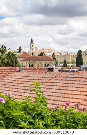 View of the red tiled roofs and cloudy sky in Jerusalem - stock photo